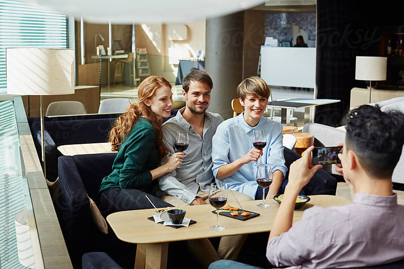 Man Photographing Happy Friends In Restaurant by ALTO IMAGES for Stocksy United