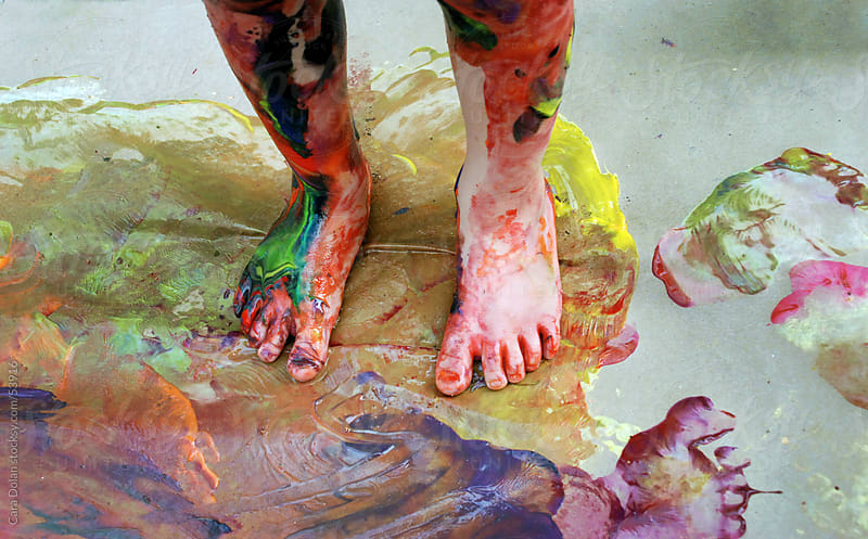 Child's legs and feet are covered in messy paint by Cara Dolan for Stocksy United