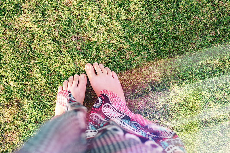 teenager selfie of feet in the grass, with light leak by Gillian Vann for Stocksy United