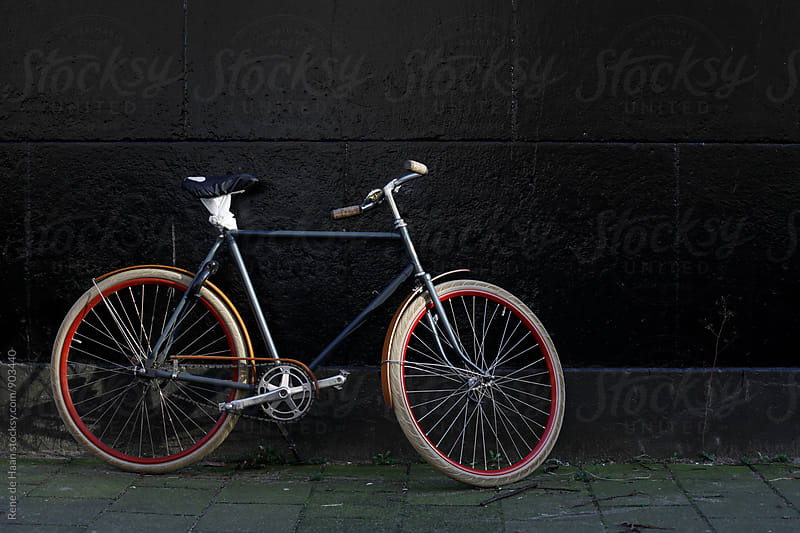 bike against black wall by Rene de Haan for Stocksy United