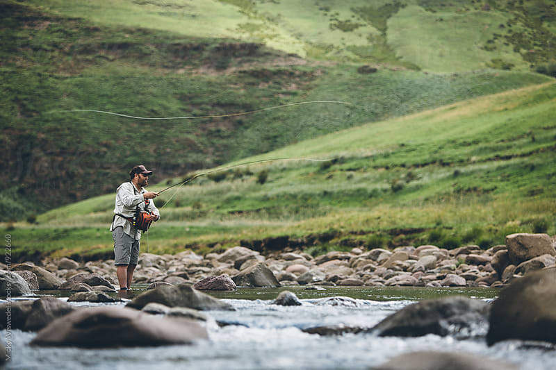 fly fisherman casting into a mountain river by Micky Wiswedel for Stocksy United