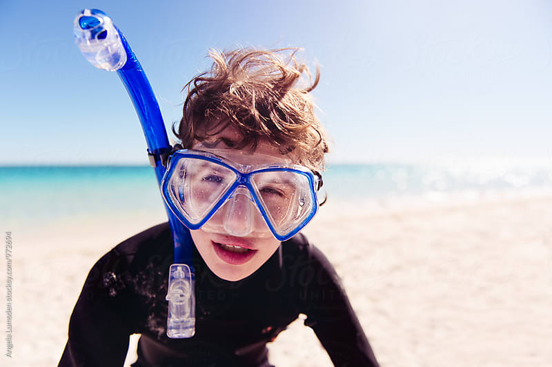 Close up of a boy with his face squished into a snorkel set mask by Angela Lumsden for Stocksy United