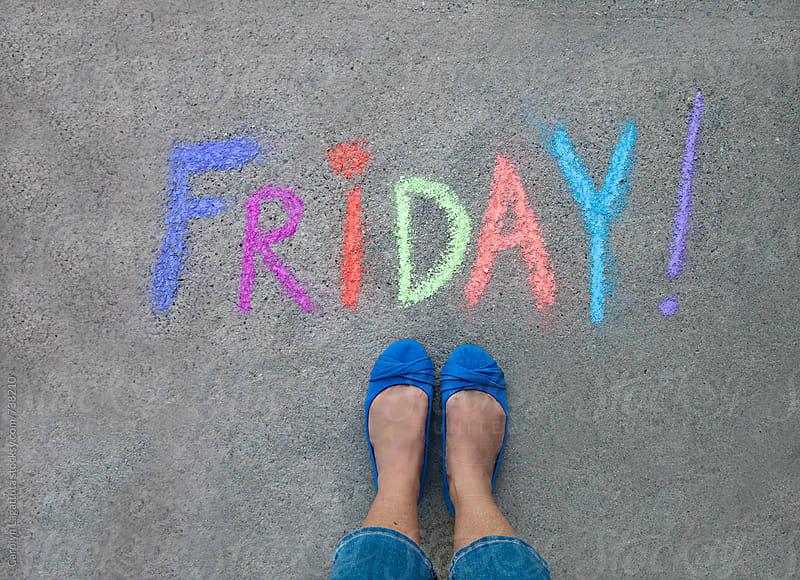 Female's feet standing above a chalk message saying Friday! by Carolyn Lagattuta for Stocksy United