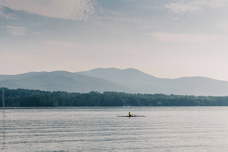 Man Alone Rowing on Lake by Raymond Forbes LLC for Stocksy United