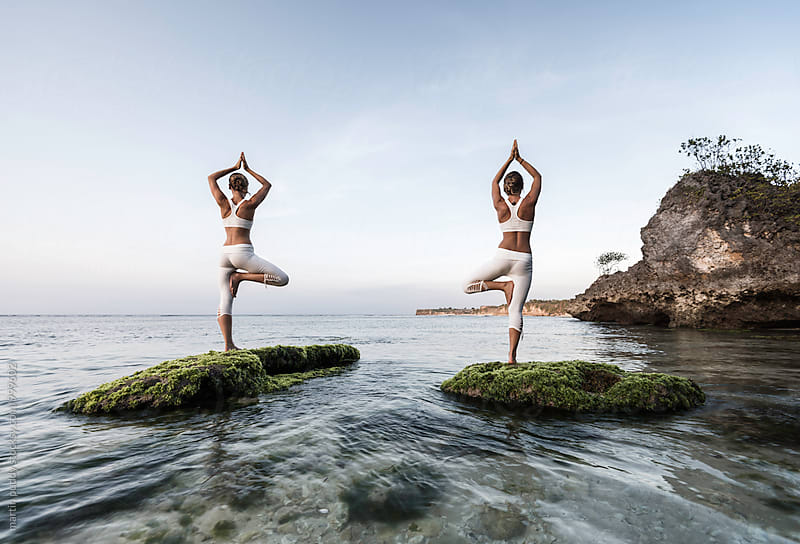 women practicing yoga at sea shore by martin puddy for Stocksy United
