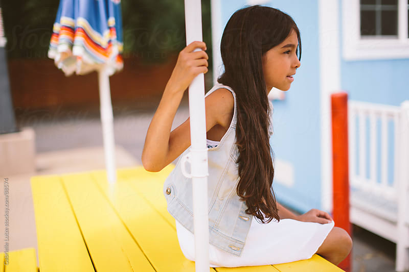 Young Girl Sitting at a Yellow Picnic Table by Gabrielle Lutze for Stocksy United