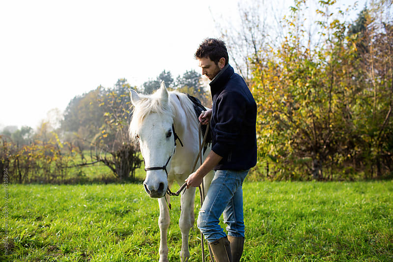 Man with his horse in a meadow by michela ravasio for Stocksy United