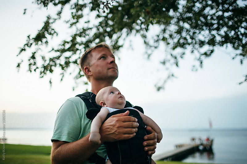 father holding a baby who is mesmerized by a tree by Kelly Knox for Stocksy United
