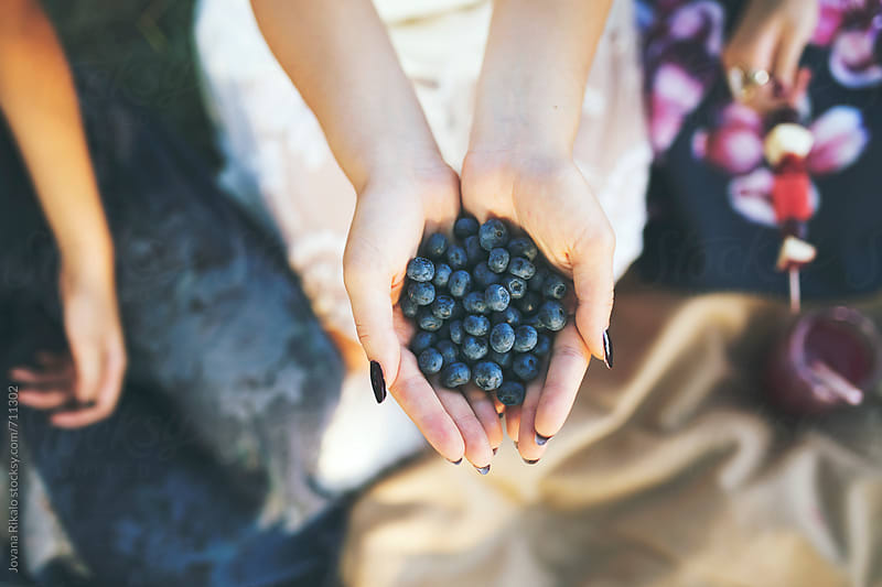 Young woman holding hands full of blueberries by Jovana Rikalo for Stocksy United