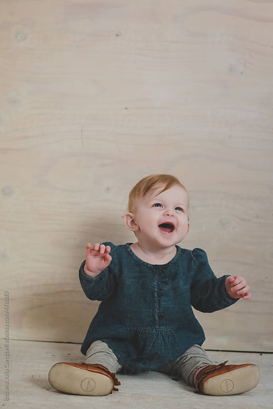 Cute baby girl smiling with wood wall background by Rob and Julia Campbell for Stocksy United