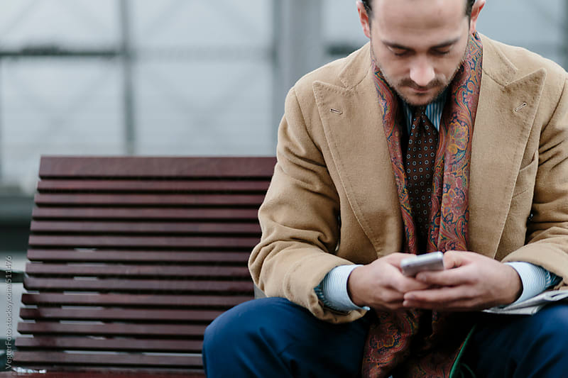 Businessman With Smart Phone Sitting On Bench by VegterFoto for Stocksy United