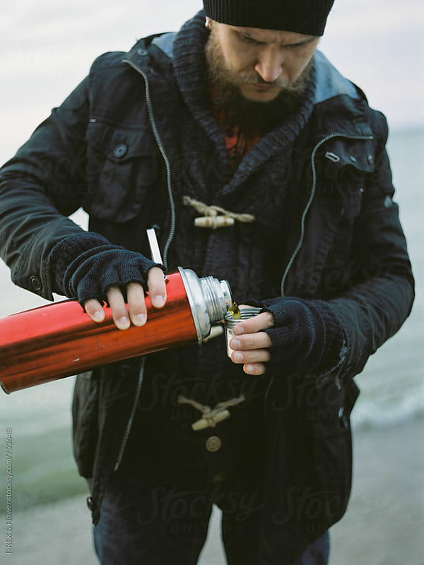 Man filling metal cup with tea by Danil Nevsky for Stocksy United