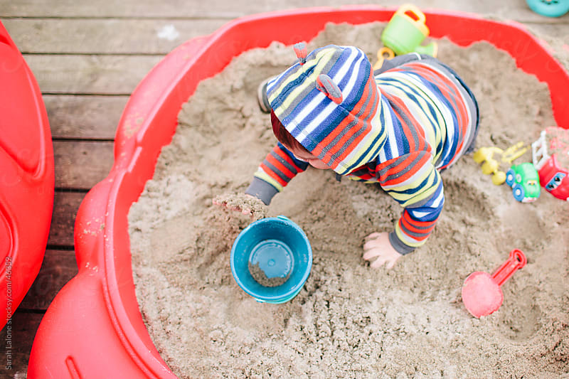 A little boy playing in a small sandbox. by Sarah Lalone for Stocksy United