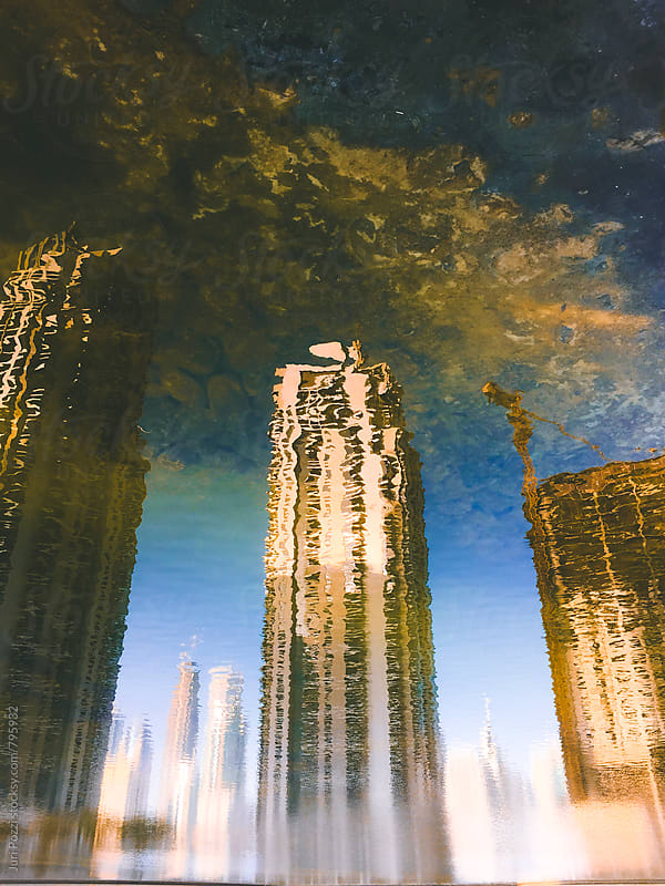 buildings reflected on a lake by Juri Pozzi for Stocksy United