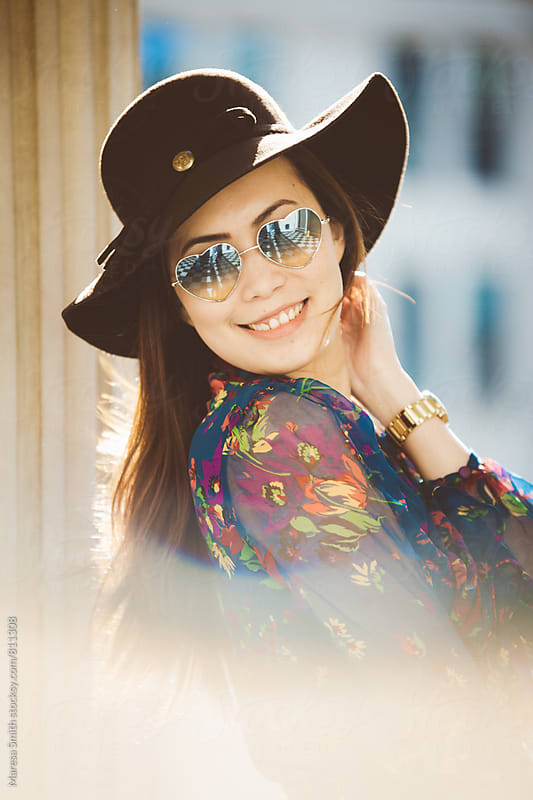 Smiling happy young lady in a floppy hat in the afternoon light by Maresa Smith for Stocksy United