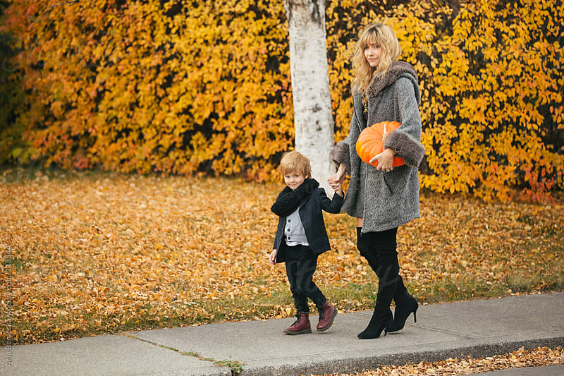 A mother and son walking on a sidewalk holding a pumpkin smiling by Ania Boniecka for Stocksy United