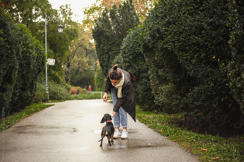 Woman playing with her dog in a park by Marija Kovac for Stocksy United