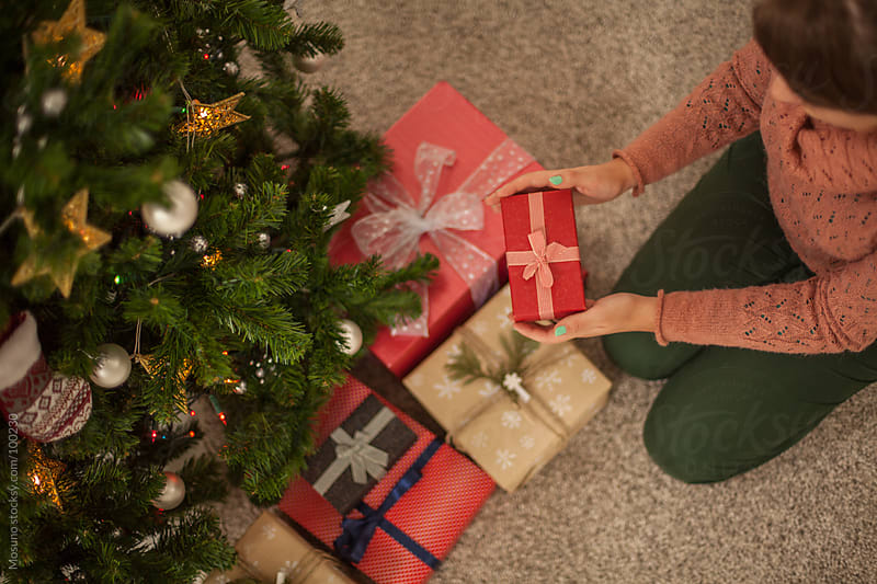 Woman Arranging Gifts Under the Christmas Tree by Mosuno for Stocksy United