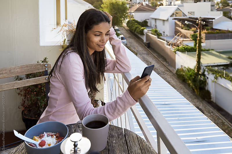 Woman using phone on balcony at home by Daxiao Productions for Stocksy United