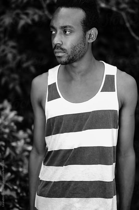 African american young man with stripes shirt in black and white by Leandro Crespi for Stocksy United