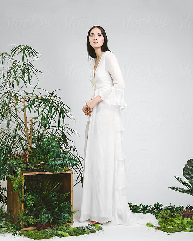 A beautiful woman in a floor lenght wedding dress by Ania Boniecka for Stocksy United
