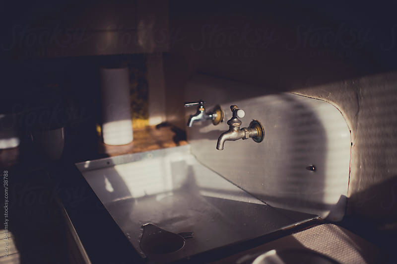 Vintage sink with two taps in afternoon light by Rachel Bellinsky for Stocksy United