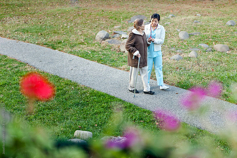 Caregiver Walks with Senior Citizen Patient by Joselito Briones for Stocksy United