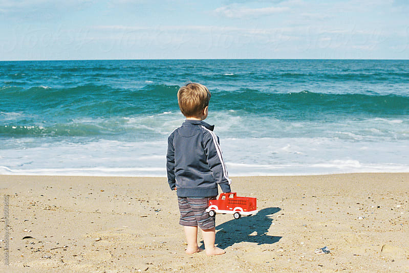 Cute young boy standing on a beach holding a fire truck staring out over an ocean by Jakob for Stocksy United