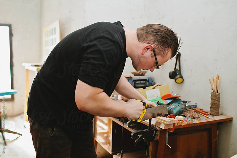Male carpenter sawing wood using a hacksaw by Sergey Filimonov for Stocksy United