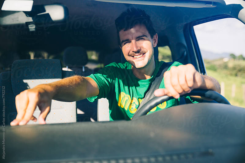 Front view from the outside of young man driver inside van during a road trip on a sunny day by Alejandro Moreno de Carlos for Stocksy United