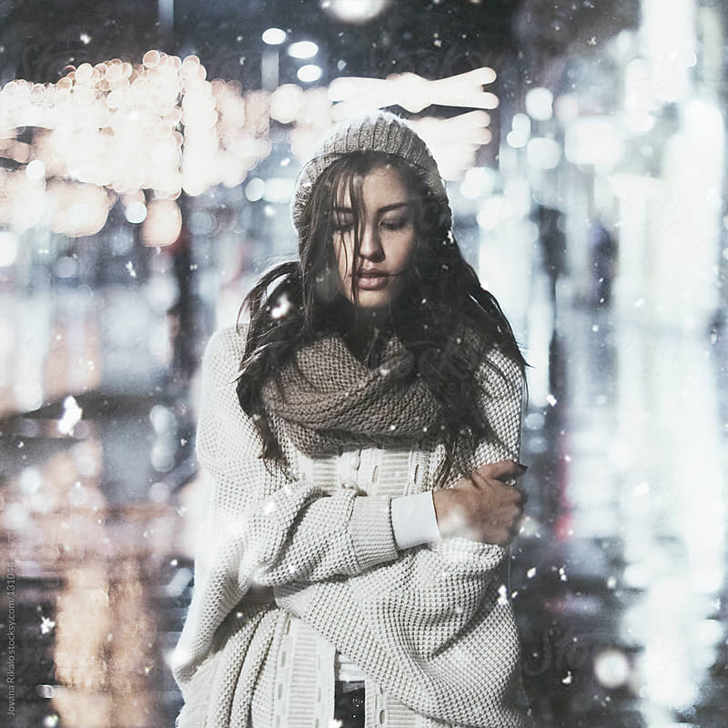 Young girl standing outsite while snowing by Jovana Rikalo for Stocksy United