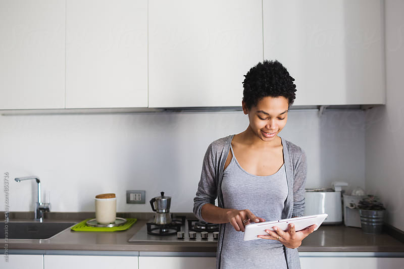 Beautiful woman using digital tablet in her kitchen by michela ravasio for Stocksy United