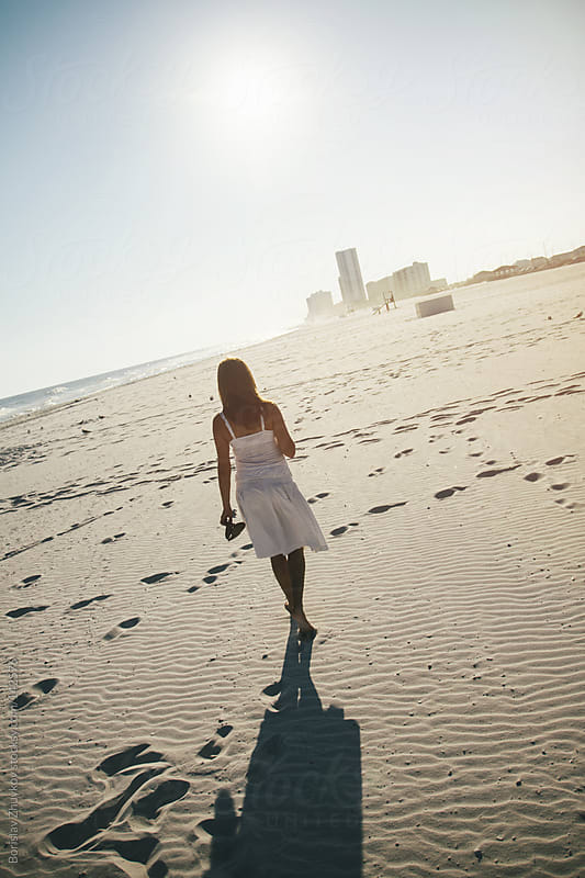 Young woman walking on the beach by Borislav Zhuykov for Stocksy United