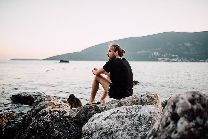 Young bearded man sitting near the sea by Boris Jovanovic for Stocksy United