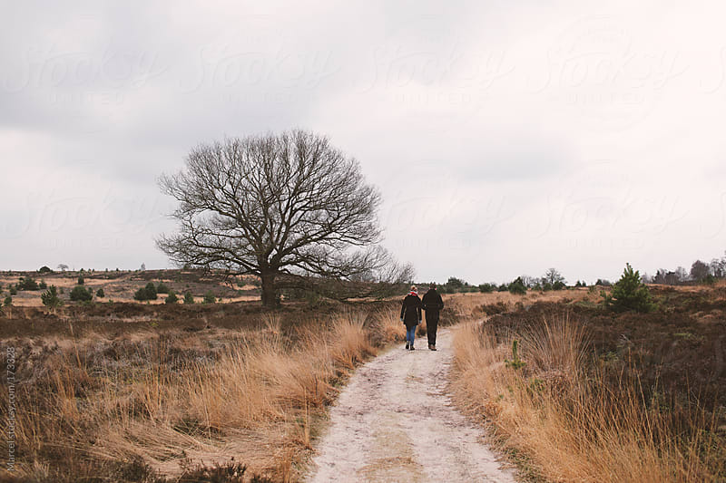 Young couple walking on a sand path between moorland by Marcel for Stocksy United