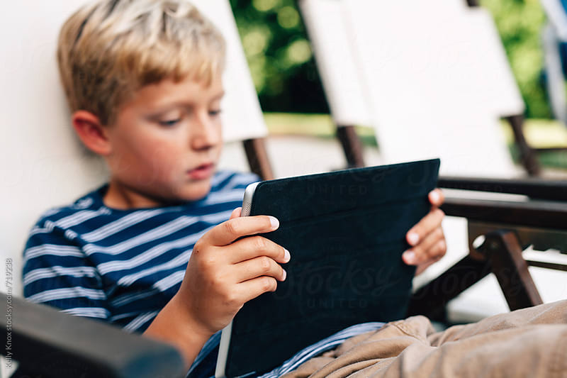 boy concentrating on his electronic device  by Kelly Knox for Stocksy United