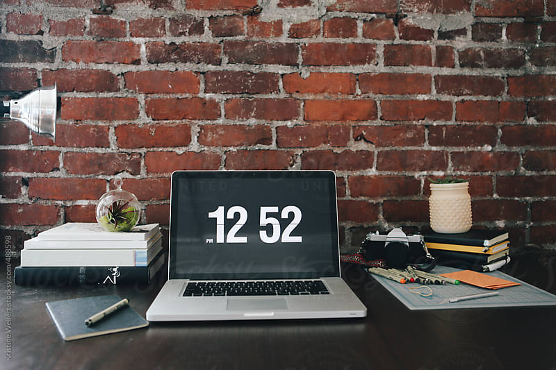 Organized desk with laptop in front of brick wall by Kristine Weilert for Stocksy United