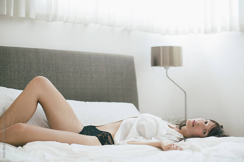 A beautiful woman lying down on a bed relaxing in her underwear by Ania Boniecka for Stocksy United