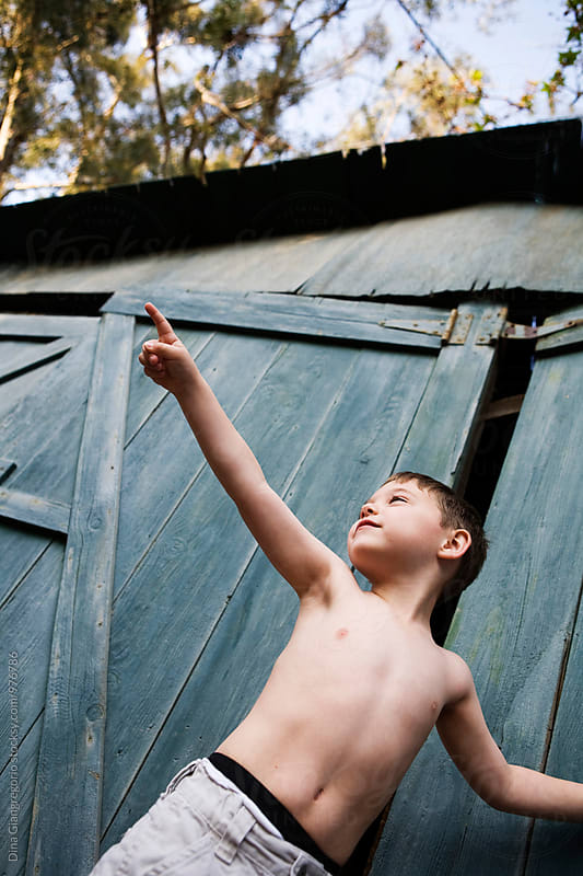 Shirtless Boy In Front Of A Blue Barn Pointing by Dina Giangregorio for Stocksy United