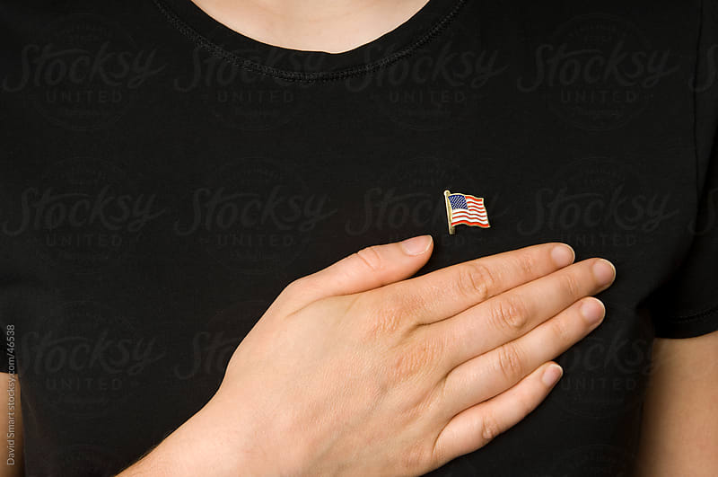USA Flag Lapel Pin, dark knit shirt, Hand by David Smart for Stocksy United