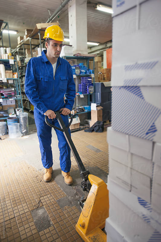 Warehouseman Operating a Manual Forklift by Lumina for Stocksy United