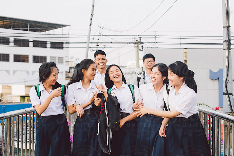 Thai students walking together on the bridge in Bangkok by Nabi Tang for Stocksy United