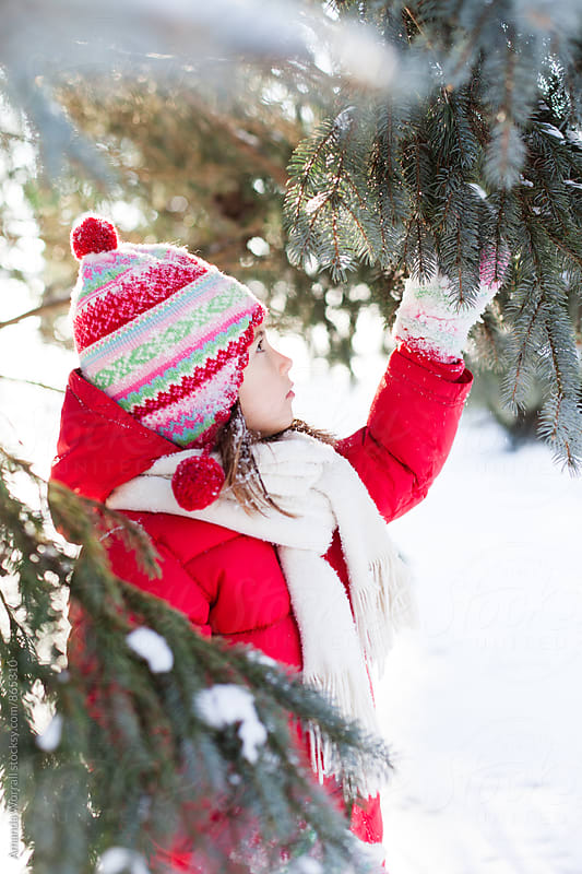 Side view of young girl wearing red coat looking at pine boughs, discovering nature by Amanda Worrall for Stocksy United