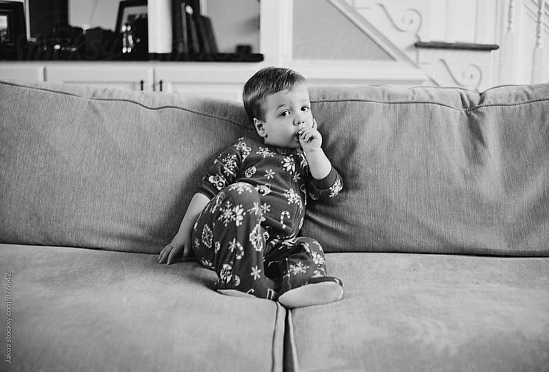 Cute boy toddler in a onesie sitting on a coach sucking his thumb by Jakob for Stocksy United