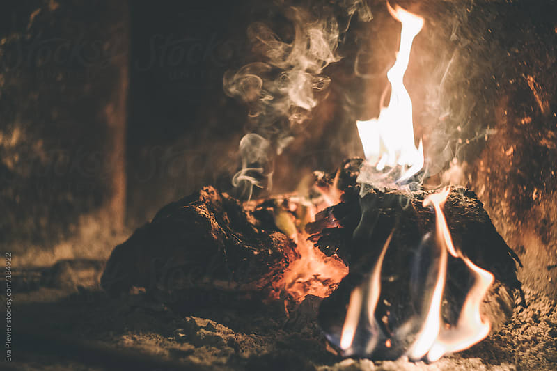 Log burning in fireplace. by Eva Plevier for Stocksy United