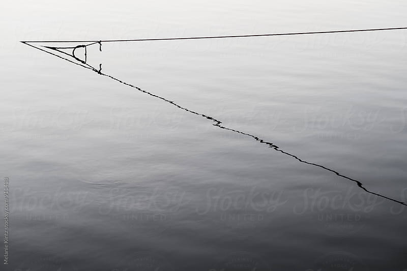 Rope leading into water with its reflection by Melanie Kintz for Stocksy United