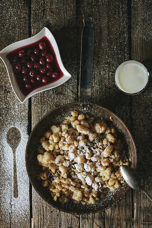 baked semolina porridge in a cast iron pan served with stewed cherries and milk from above by Leander Nardin for Stocksy United