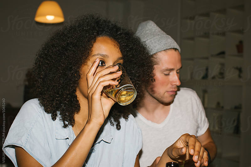 Snapshot of Mixed Race Woman Drinking a Glass of Beer at Informal Dinner Party by Julien L. Balmer for Stocksy United