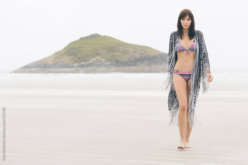 A woman in a pink bikini walking toward the camera on a cloudy beach by Ania Boniecka for Stocksy United