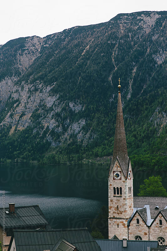 Church tower at mountain lake by Andrey Pavlov for Stocksy United
